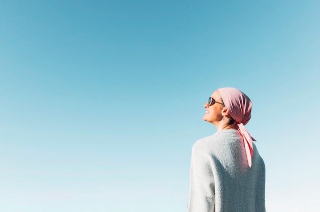 Frau mit rosa kopftuch, hat krebs