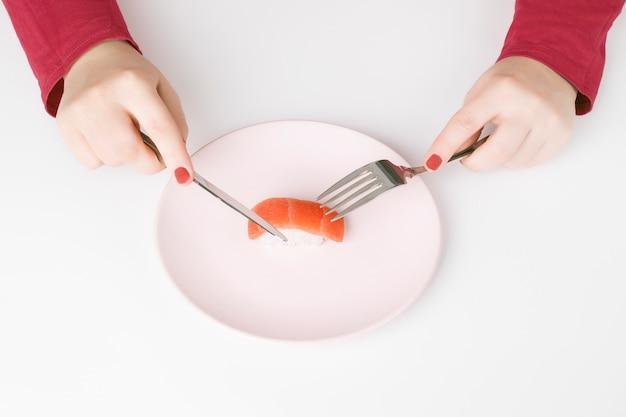 Frau mit rosa nägeln und dunkelrosa strickjacke ungefähr, zum eines stückes lachssushi mit tischbesteck auf einer rosa platte zu essen