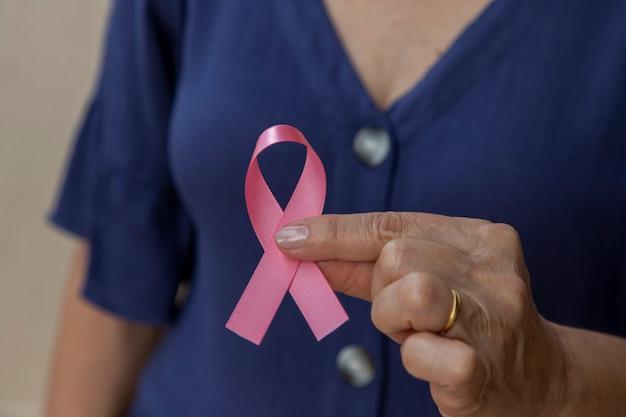 Frau mit rosa schleife in der hand. kampagne zur brustkrebsvorsorge. rosa oktober