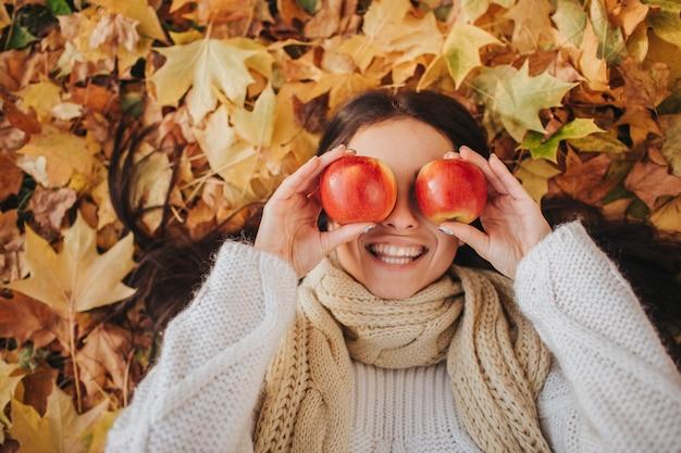 Frau mit rotem apfel im herbstpark. saison-, frucht- und personenkonzept - schönes mädchen, das auf boden und herbstlaub liegt. weibliches model hat spaß im herbst.