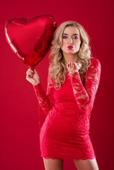Frau mit rotem ballon, der einen kuss bläst