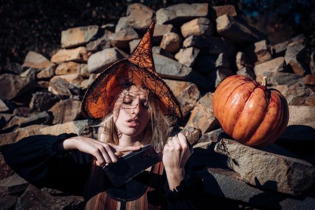 Frau mit rotem blut und blonden haaren. furchtsames blutiges mädchen im orangefarbenen hut des zauberers mit kürbis. halloween-party-kunstdesign. satz lustige halloween-elemente. furchtlosigkeit konzept.