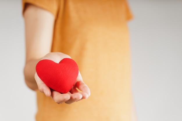 Frau mit rotem herz, liebe, krankenversicherung, spende, glücklicher wohltätigkeits-freiwilliger, welttag der psychischen gesundheit, weltherztag, valentinstagvalent