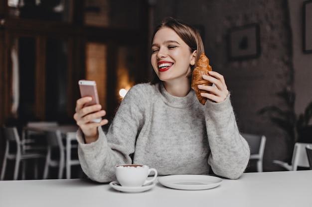 Frau mit rotem lippenstift lacht beim chatten im smartphone. porträt der dame im grauen pullover mit croissant in ihren händen.