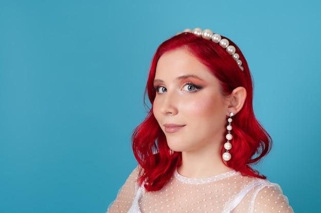 Frau mit rotem welligem haar in einem weißen kleid, perlenstirnband und langen baumelnden ohrringen