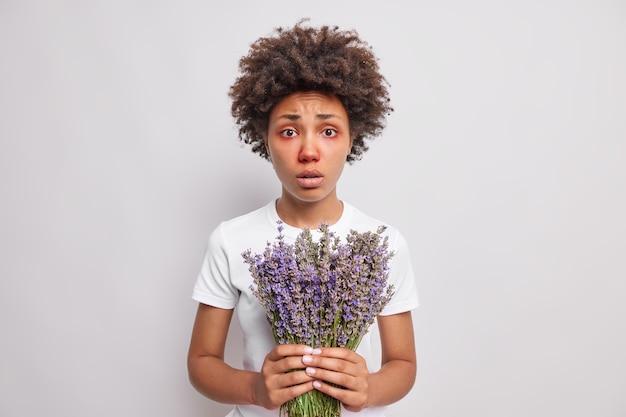 Frau mit roten augen hält lavendelstrauß hat allergiesymptome, die überempfindlich sind, trägt lässiges t-shirt isoliert über weiß