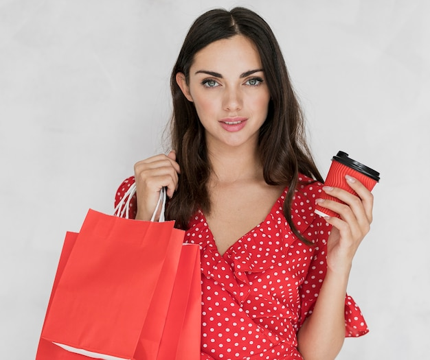 Frau mit roten einkaufstüten und kaffee