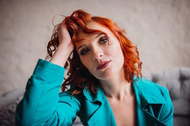 Frau mit roten haaren sitzt müde in ihrem blauen mantel