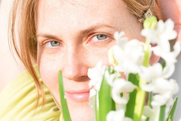 Frau mit roten haaren und sommersprossen und strauß weißer blumen
