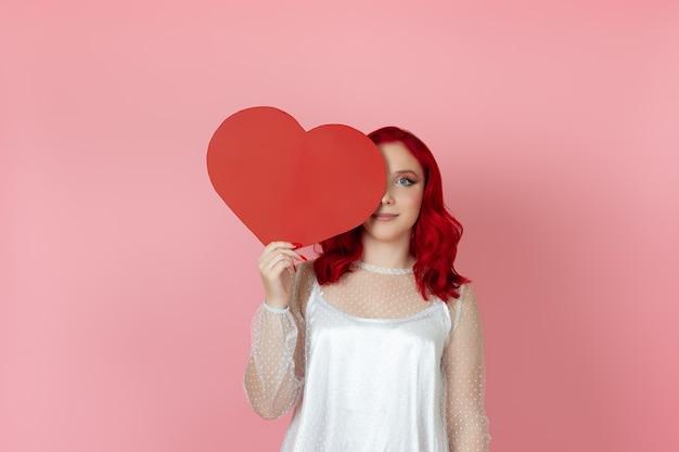 Frau mit roten haaren versteckt die hälfte ihres gesichts hinter einem großen papierroten herzen
