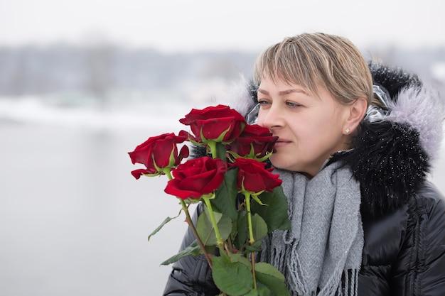 Frau mit roten rosen draußen im winter