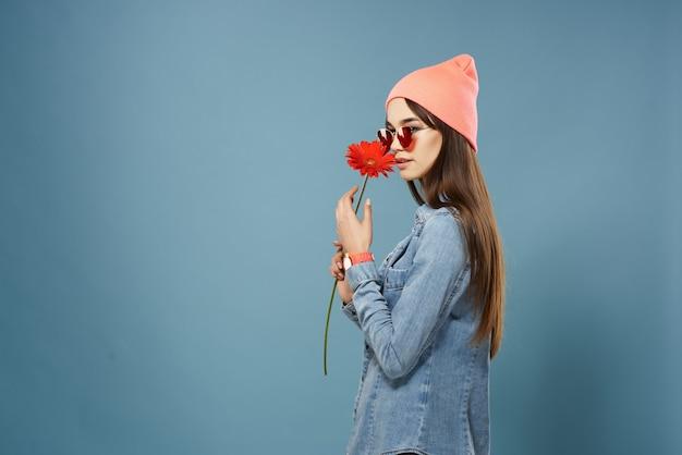 Frau mit roter blume in den händen rosa hut modische kleidung glamour
