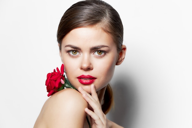 Frau mit roter blume rote lippen glamour vorwärts schauen helles make-up beschnittene ansicht