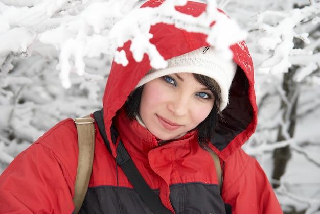 Frau mit roter jacke und handschuhen im schneewald
