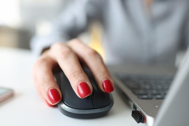 Frau mit roter maniküre, die computermaus nahe laptop-nahaufnahme hält