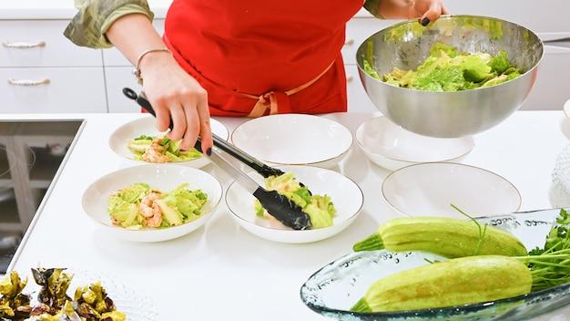 Frau mit roter schürze, die in einer weißen küche kocht