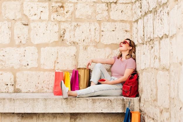 Frau mit roter sonnenbrille, die auf der straße ihrer stadt ruht, umgeben von bunten taschenkonzepten, die süchtig nach einkaufen, verkäufen und angeboten sind. lebensstil.