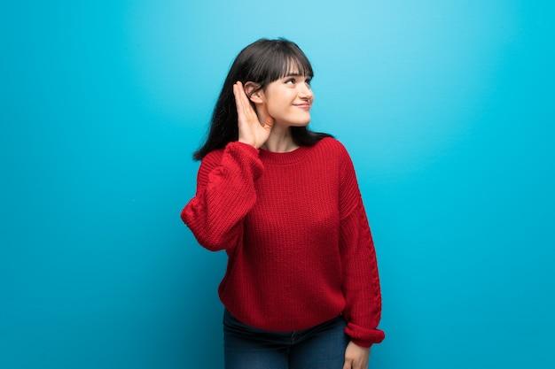 Frau mit roter strickjacke über blauer wand hörend auf etwas, indem sie hand auf das ohr setzen