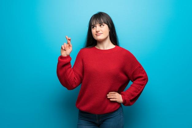 Frau mit roter strickjacke über blauer wand mit den fingern, die das beste kreuzen und wünschen