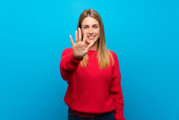 Frau mit roter strickjacke über der blauen wand, die fünf mit den fingern zählt
