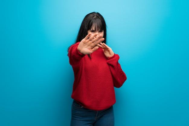 Frau mit roter strickjacke über der blauen wand nervös und erschrocken, hände zur front ausdehnend