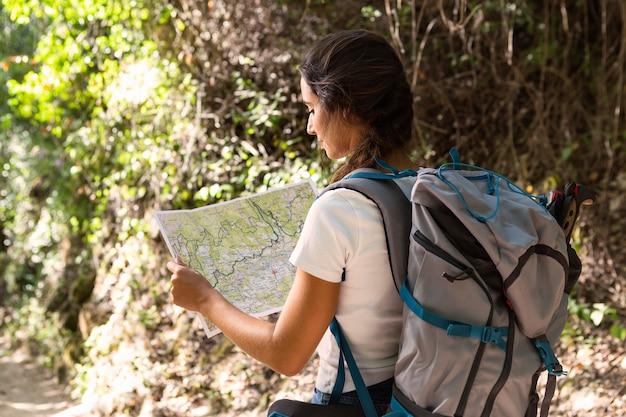 Frau mit rucksack auf einem naturabenteuer unter verwendung der karte