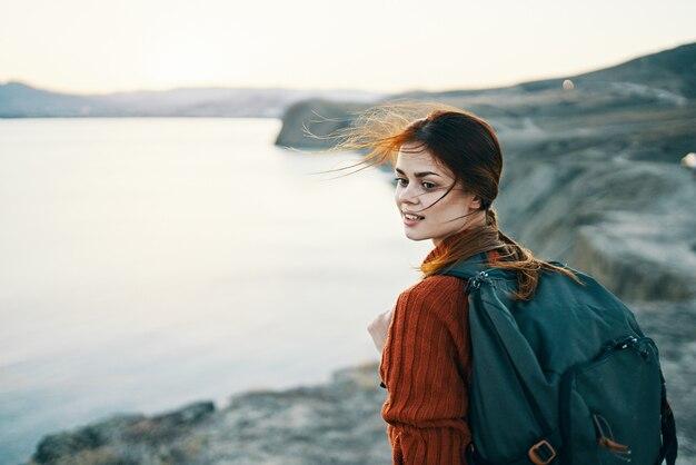Frau mit rucksack auf natur in den bergen nahe dem meer bei sonnenuntergang