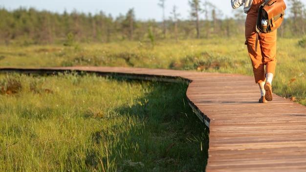 Frau mit rucksack auf ökologischem wanderweg im sommer, abgeschnittener schuss. naturforscher, der wildtier- und ökotourismus-abenteuer auf dem weg erkundet