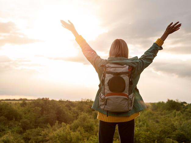 Frau mit rucksack bei sonnenuntergang in der natur