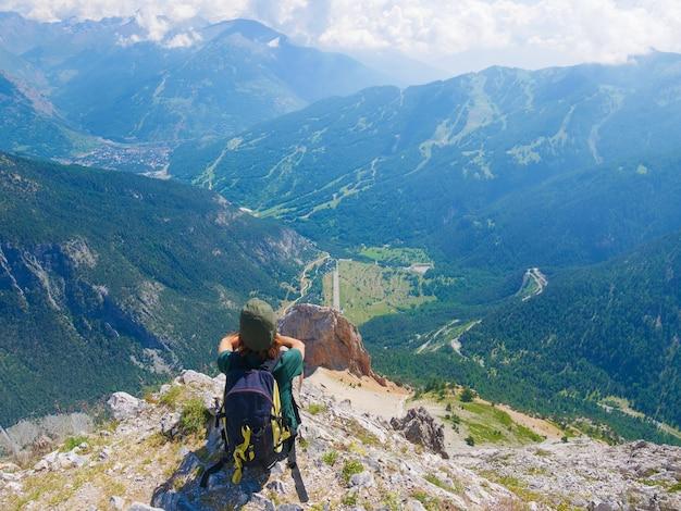 Frau mit rucksack, der auf berggipfel ruht, ansicht dramatisches landschaftstal-sommeraktivitäts-fitness-wohlfühlfreiheitskonzept betrachten, selektive fokusrückansicht