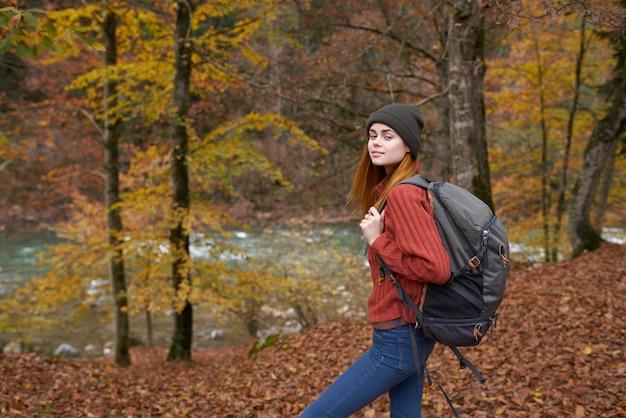 Frau mit rucksack, der im herbstpark nahe dem fluss in der naturseitenansicht geht