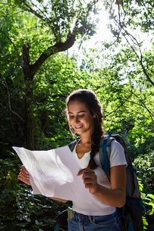 Frau mit rucksack, der natur beim betrachten der karte erkundet