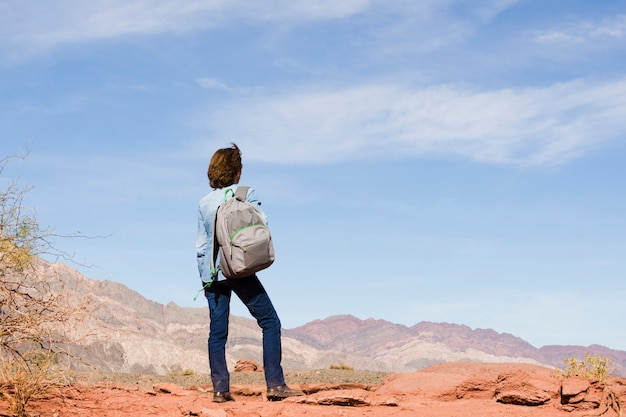 Frau mit rucksack die landschaft bewundernd