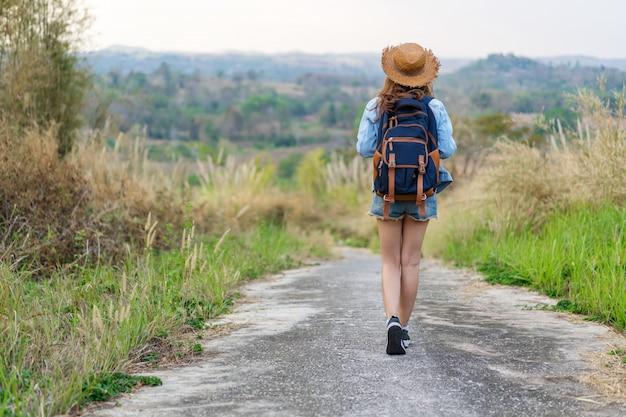 Frau mit rucksack gehend auf fußweg in der natur