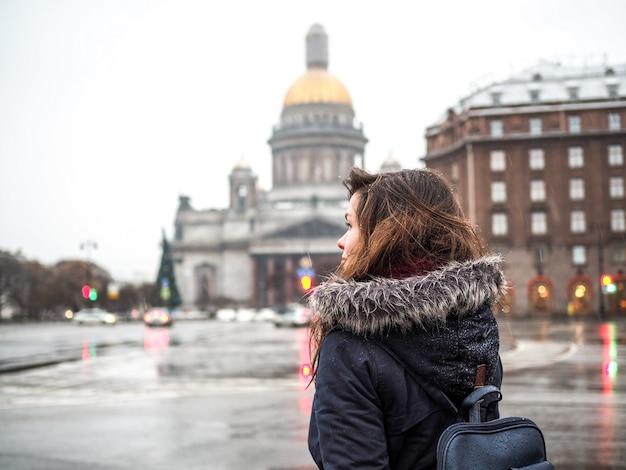 Frau mit rucksack mit blick auf die isaakskathedrale und den hauptplatz in sankt petersburg