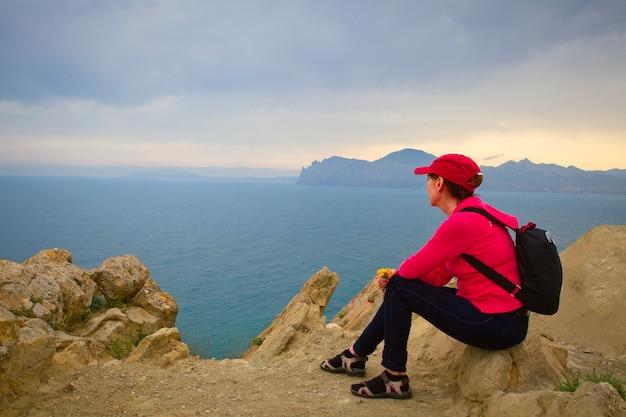 Frau mit rucksack oben auf dem berg betrachtet die seelandschaft