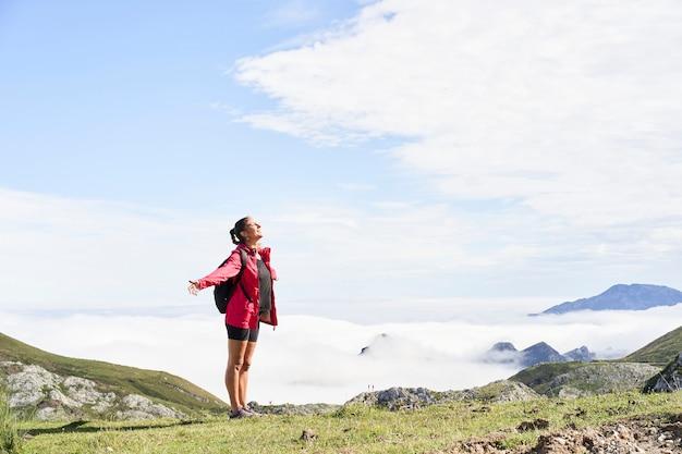 Frau mit rucksack stehend und mit offenen armen oben auf einem berg und irgendwo schauend. er trägt eine rote jacke. im hintergrund sieht man berge, die von nebel umgeben sind.