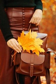 Frau mit rucksack und blättern in der hand bouquet von herbstlichen gelben blättern stilvolle frau in einem burgun... Premium Fotos