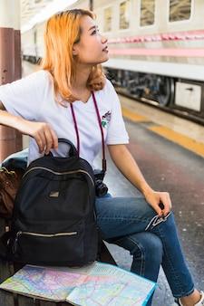 Frau mit rucksack und kamera auf bank auf plattform