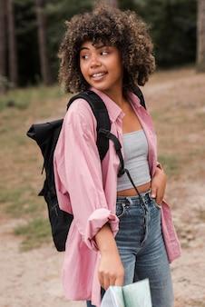 Frau mit rucksack und karte im freien
