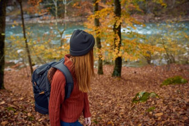Frau mit rucksackreisetourismus waldlandschaftspark fluss gefallen blätter seitenansicht
