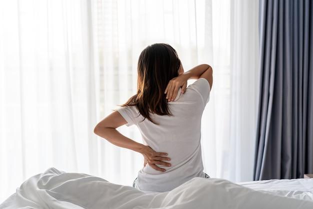 Frau mit rücken- und nackenschmerzen auf dem bett, gesundheitsversorgung und problemkonzept Premium Fotos