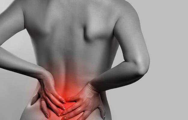 Frau mit rückenschmerzen, schmerzen zurück auf grauem hintergrund isoliert. skoliose. rückenmarkprobleme auf dem rücken der frau. monochromes foto mit rot als symbol für die aushärtung