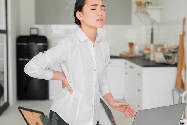 Frau mit rückenschmerzen von der arbeit