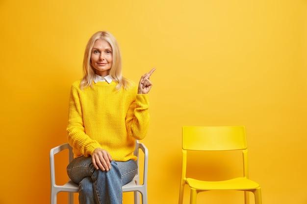 Frau mit ruhigem gesichtsausdruck trägt pullover und jeans posiert auf stuhl zeigt oben rechts allein verbringt zeit allein