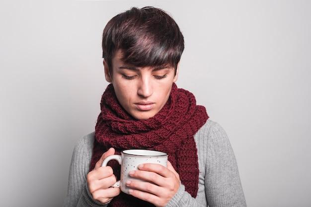 Frau mit schal um ihren hals, der kaffeetasse betrachtet