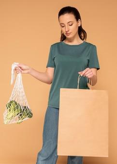 Frau mit schildkrötenbeutel und papiertüte