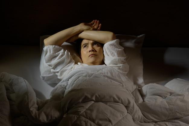 Frau mit schlaflosigkeit, die mit offenen augen im bett liegt