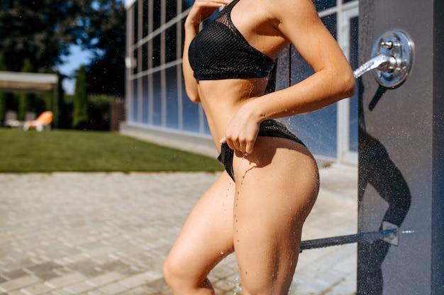 Frau mit schlankem körper, der eine dusche nahe dem pool im freien hat.