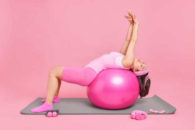 Frau mit schlanker figur beugt sich über fitnessball hebt arme streckt körper hält die augen geschlossen posen auf matte benutzt sportgeräte